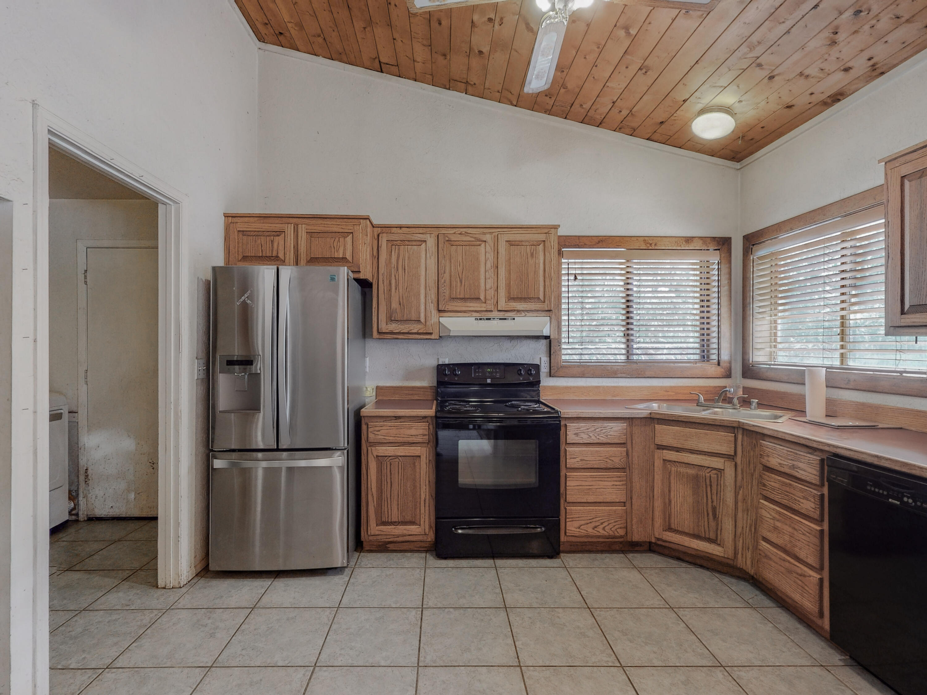 Great Split level Home on a Wooded Lot, get away from it all! This wonderful home is bermed concrete with passive solar, and with the wood burning stove it keeps toasty in the winter with low utility costs. Home needs some TLC, it's been vacant but maintained the last 2.5 years. Great Bones & Structure, beautiful hardwood floors, T&G ceilings, it needs carpet, paint, bathroom updates, cosmetics inside. Tranquillo Pines water, metal roof, appliances stay, 2 storage sheds, completely fenced and gated oversized garage 20X20 with double doors and work space. Plenty of Equity here!