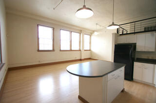 Approximately 727 square feet, this first floor loft in the historic 1938-built Classroom building at The Lofts at Albuquerque High features the original wood floors, 4 operable wooden windows with a  view of downtown, 13-foot-tall ceilings, island kitchen, contemporary light fixtures and ceiling fan, full bath with tub and ceramic tile floors, and custom closet. Elevator in building. Laundry/exercise facility. Condo Association dues covers water/sewage/trash/recycling, insurance, common area maintenance and reserve fund contribution. Association allows 1 dog no more than 30 lbs or 2 dogs with combined weight of no more than 30 lbs. Pets limited to dogs, cats, fish and birds. No Airbnb or similar type short-term rentals.