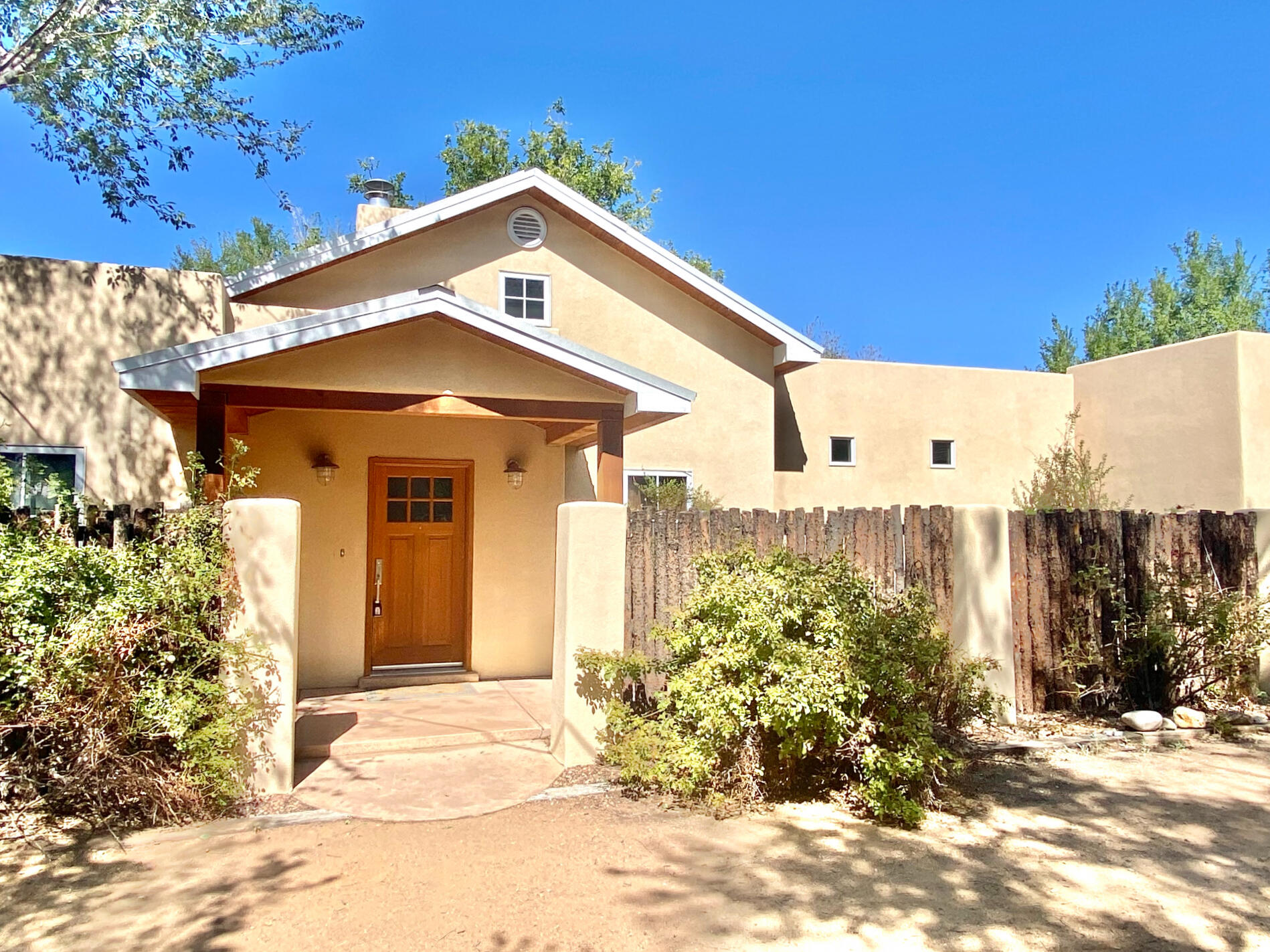 Nestled on a 1/2 AC in the desirable N. Valley, this quaint 3 BR/2 BA home is filled with happy hues, vibrant colors, tall ceilings, concrete floors and large FP, adding to the contemporary flair. The open plan flows into the living, dining and galley kitchen, featuring stainless appliances, multi-colored cabinets, Silestone countertops, and pantry.  Laundry w/full-size washer/dryer and storage closet lead to the expanded, heated 2-Car garage. Enjoy the fully-fenced gated yard with lots of parking, large storage shed, and secluded courtyards surrounded by coyote/cedar fencing with rock water feature. Experience serenity in the N. Valley while close to outdoor activities, walking/bike trails, open space, Rio Grande, shopping, restaurants, grocery stores, malls, I-25 and Balloon Fiesta Park