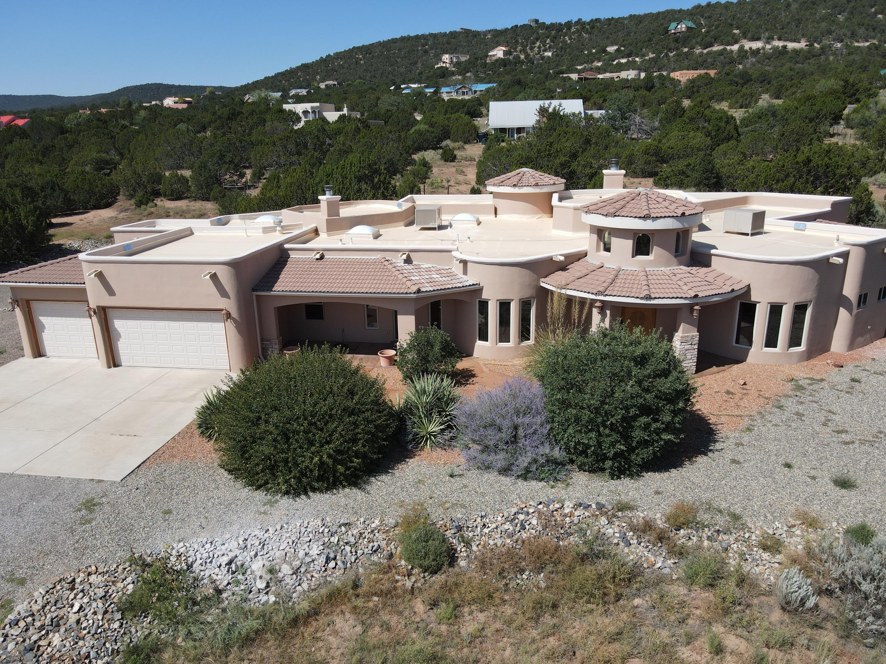 Welcome to an Estate of Sandia Mountain Ranch!  This highly sought after subdivision is the GEM of the East Mountains!  This one owner, custom built home is nestled on over TWO ACRES of Mountain Real Estate!  The spacious floor plan features FIVE large bedrooms, four of the bedrooms and en-suite bathrooms, an incredible master suite with a cozy fireplace, garden tub, separate shower, HUGE walk in closet, patio access, a finished and oversized three car garage, storage room, radian heat, NEW  T.P.O. ROOF SYSTEM, NEW MASTER COOL UNITS, T&G ceiling in the Great Room, ALL Upgraded appliances, and over 1600 square feet of covered patio !!!!Come see this amazing property TODAY!
