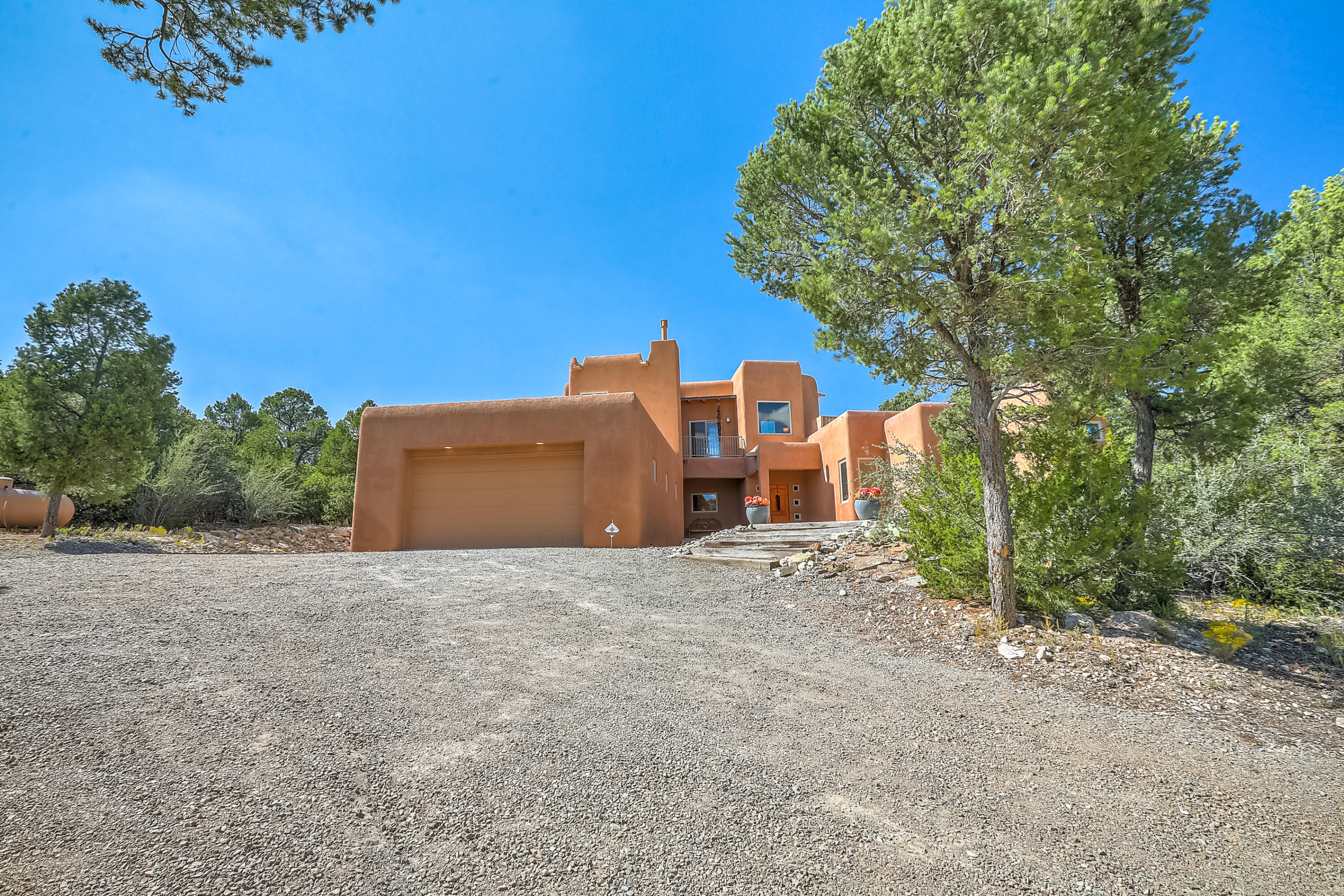 Luxury Mountain Living just 20 minutes from the city in the Coveted Rancho Verde subdivision! This densely forested lot smells of sweet pinon trees!  Quality construction with flagstones walkway. The home greets you with warmth and a grand, curved staircase with designer mosaic. Open chef's  kitchen with island, pantry, custom cabinets, granite slab countertops and stainless steel appliances. Spacious semi-formal dining space! Generous Great room with tongue and groove ceilings with vigas, classic kiva style fireplace and back patio access. Energy saving pellet stove. Conveniently located downstairs is the Primary Suite with its own upscale bath featuring dual vanities, oversized garden tub, separate glass block shower and gracious walk-in closet! Upstairs boasts 2  secondary bedrooms with