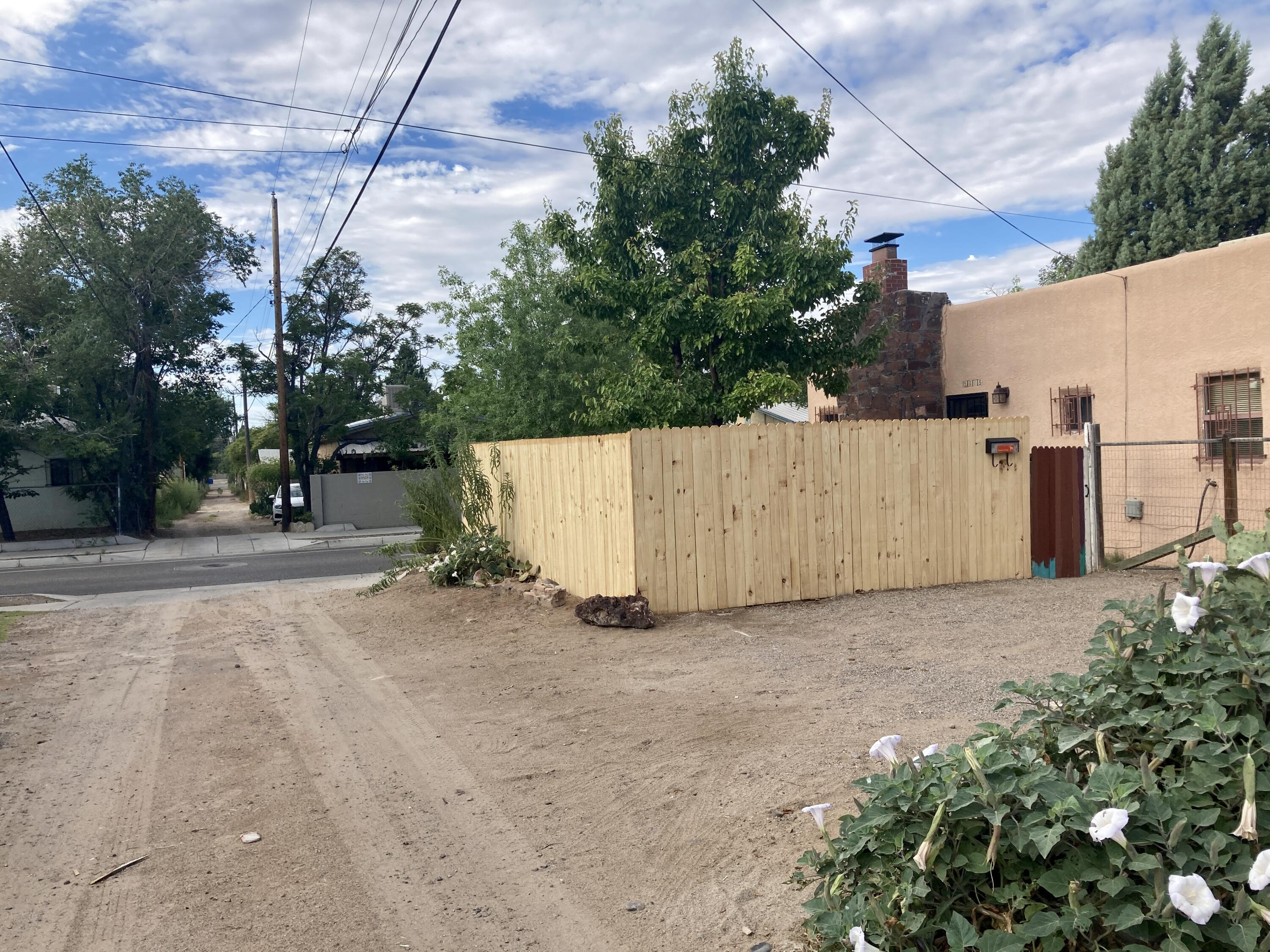 Just 3 blocks from UNM.  Charm and warmth in this 2 bedroom Pueblo with  extra space (possible third bedroom.) There is a detached old garage used as a large storage room.  Cute kitchen with checkered flooring.  Separate laundry room with washer and dryer. Full bath, fireplace, and front and back yards.  Off street parking for two cars.  Fenced and walled for privacy.  Convenient , walkable location.