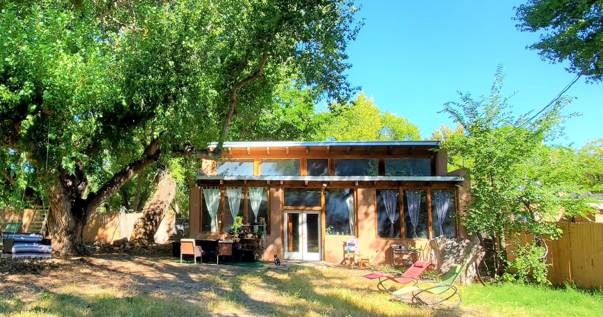 Passive solar adobe on a unique property! The last house on a dead end, nestled between giant old growth cottonwoods/elms and organic gardens situated right next to the Irrigation ditch/trails with water rights for growing...truly an oasis that is naturally green and cool. A safe retreat less than 10 minutes from downtown near Barelas, that still has plenty of privacy on .61 acre, secured with 8ft razor fencing. 15ft ceilings, adobe cemented walls and brick floor, Jacuzzi garden tub, bright kitchen including appliances and wood stoves... Insulated sunny warehouse with double garage doors at 1500 Sq Ft. which comes with ventilation hood, metal closet safe and double sinks/dishwasher and a car lift. Also a 20x8 solar building with laundry and .75 bathroom for RV guests. A rare find.