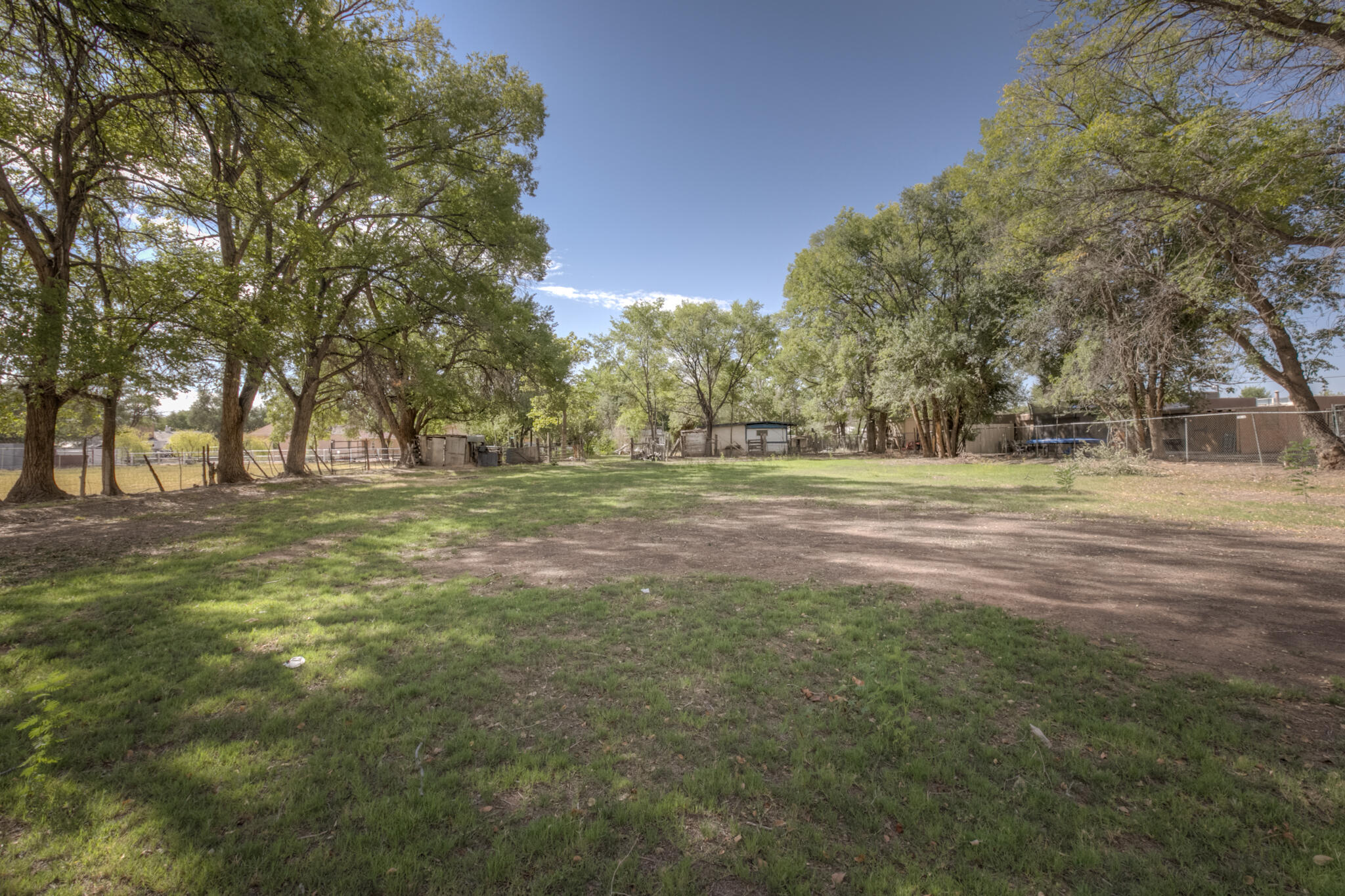 Amazing opportunity to own almost 2 acres in the lush and green South Valley! Ditch water access on property.  Mature trees, fields, pasture, two private courtyards, multiple outbuildings and tons of possibility and potential!
