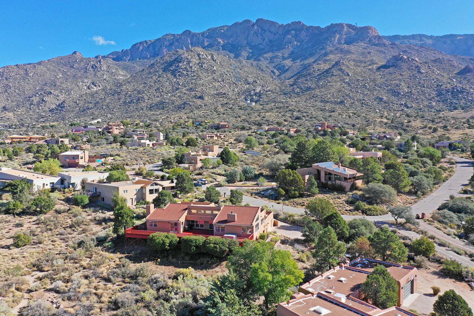A rare find in an extraordinary setting. Nestled at the base of the Sandia Mountains, this property commands a panorama of views extending as far as the eye can see over and around Albuquerque. You can sit on a quiet, enclosed patio and watch the Sandia's claim their watermelon nickname in the evenings, then watch the sunset from a broad open deck as the valley slowly lights up the night sky. The interior is bright and open with large windows and a clearstory one would hope to find in a building with such amazing views. There are 4 bedrooms, 3 bathrooms, an updated kitchen, a lower-level recreation room and an oversized 2 car garage. Come and see this property, sit quietly on the east facing patio, watch our famous tram makes its lofty trek to the top of the mountain and listen. Priceless!