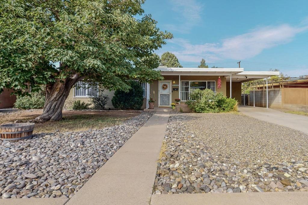 Spacious, well-maintained mid-century home on large lot in the heart of Albuquerque.  Over 1,600 sqft, 3 bed/ 2 bath home with open floor plan and abundance of natural light.  Stunning original red oak hardwood floors, living room with decorative fireplace and large picture windows offering Sandia Mountain views. Kitchen features new Hisense stainless steel refrigerator, skylight and opens to oversized den with wood-burning fireplace and large storage closet.  Covered patio and big fenced backyard with large storage shed and towering Arizona Cypress trees, providing shade and privacy.  Upgraded electrical service, thermal windows, laundry room and built-in carport.  Located one block from Zia Park, near UNM, Nob Hill, Sunport, Sprouts and Whole Foods.  Come and see - won't last long!