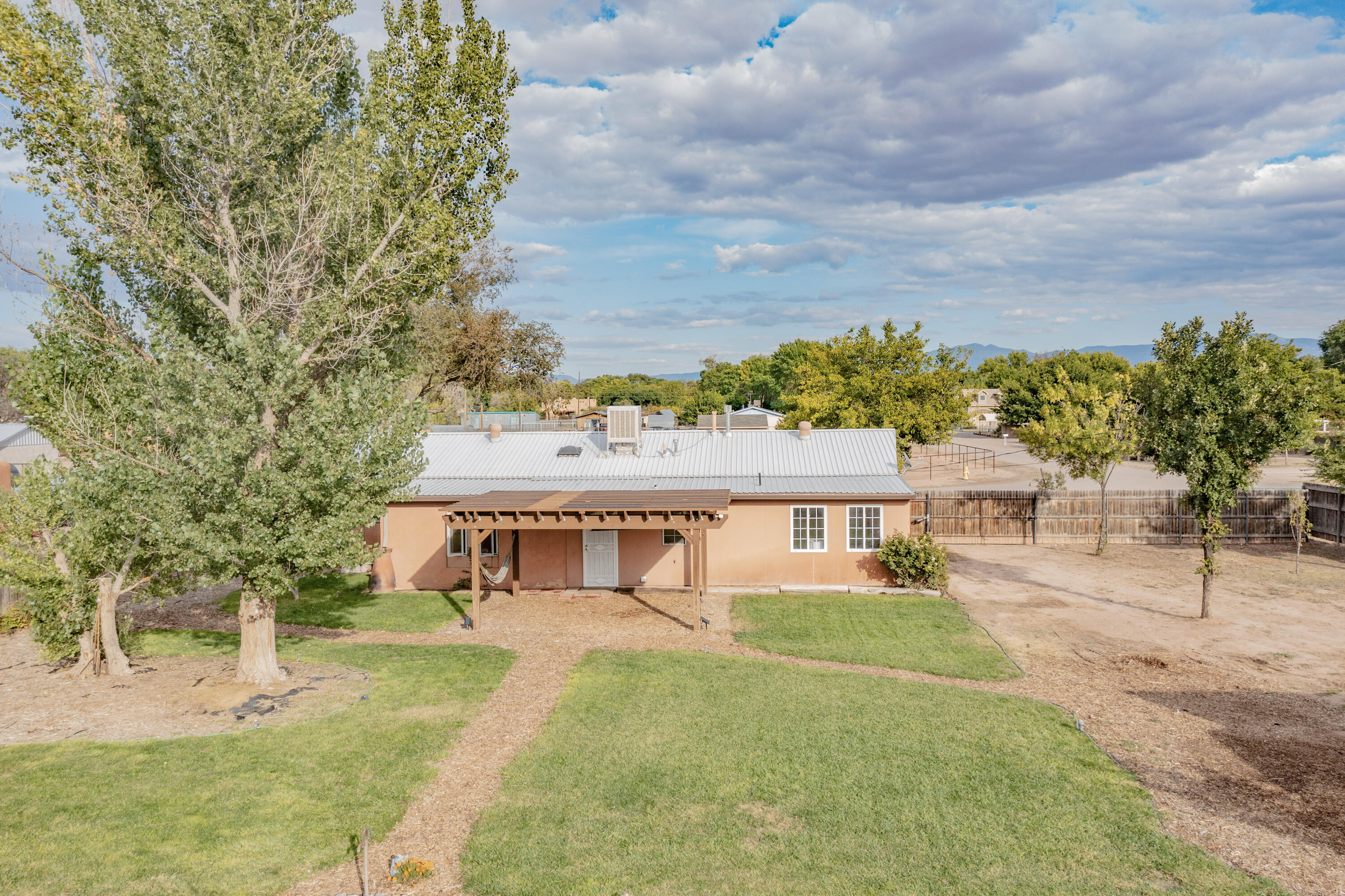 Come see this beautiful country home in Bosque Farms. 1848 SqFt, 3 bedrooms, 1.75 baths on .51 acres. It is bright and airy and has 2 living areas, an office with built-in shelves, dining and laundry rooms with tile and carpet throughout. The open central kitchen has a stamped tin backsplash and plenty of cabinets. The spacious main bedroom has a lot of natural light and looks out to the large private backyard. There is a 600 SqFt workshop/1 car garage with vaulted ceilings and room for all your toys! The fenced yard has backyard access, an irrigation well, lawn sprinklers, raised garden beds, grapes, berries and fruit trees. Relax under the shaded pergola! City utilities and no HOA. This house is close to conveniences, shopping and dining and is ready to be your home sweet home!