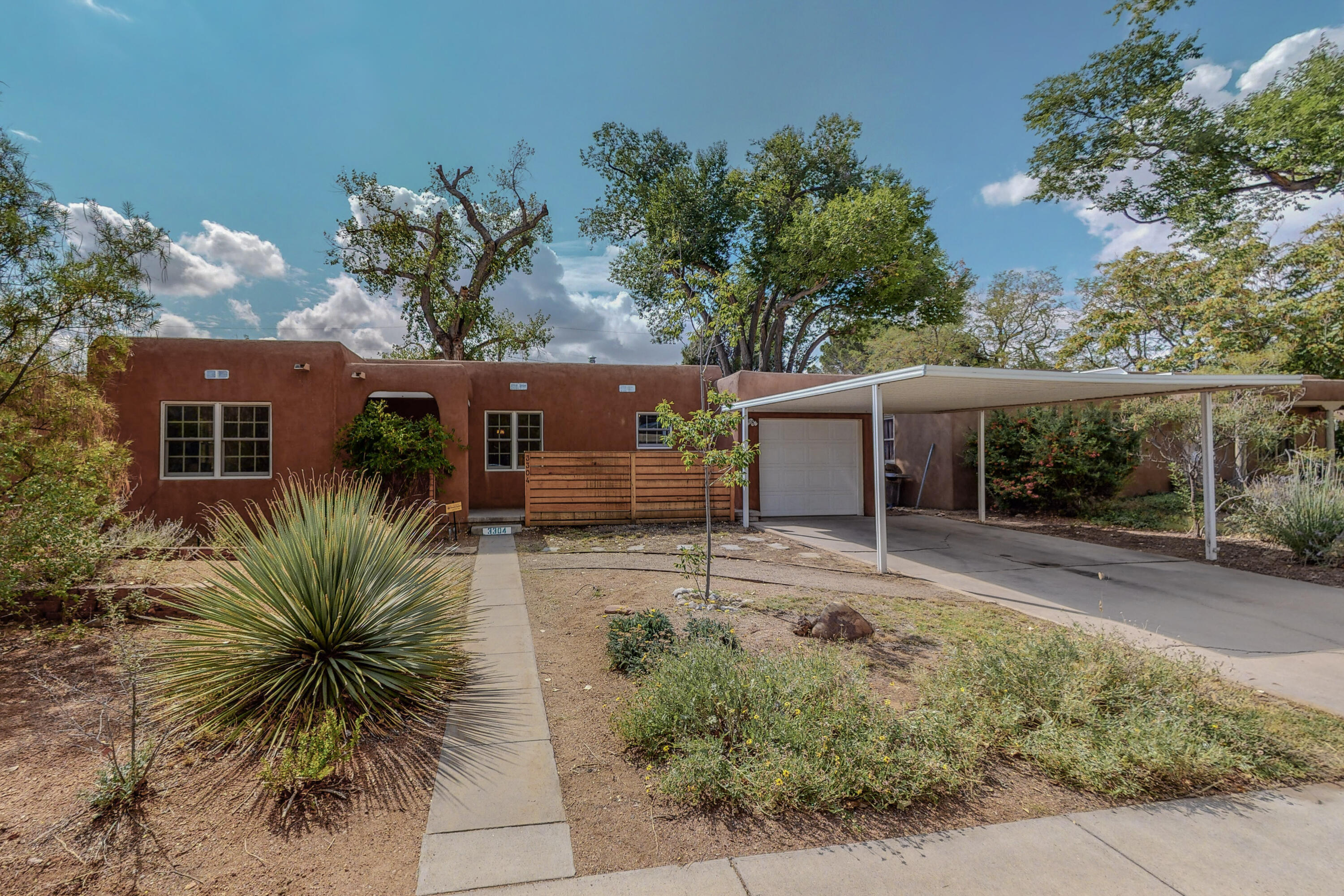 WOW! Gorgeous remodeled Pueblo with tons of character and darling curb appeal nestled in sought after UNM NORTH.  Classic features: original hardwood floors, cove ceiling & kiva FP. Kitchen remodeled with custom Maple Shaker fronts, soft close cabinets, granite counters, high end stainless appl and gas cooktop. Other features: Brand new washer and dryer, new paint, mini-splits with refrigerated air, ceiling fans, updated windows & new water heater. Owner's suite has walk-in closet, sitting room or office, classic wood ceiling & French doors leading to backyard and restful patio. You will LOVE the huge yard with above ground pool, raised beds for gardening, large shed, party lights and gated walled yard for privacy. This gem, just minutes to UNM and Bataan Park, is a true find. MUST SEE!