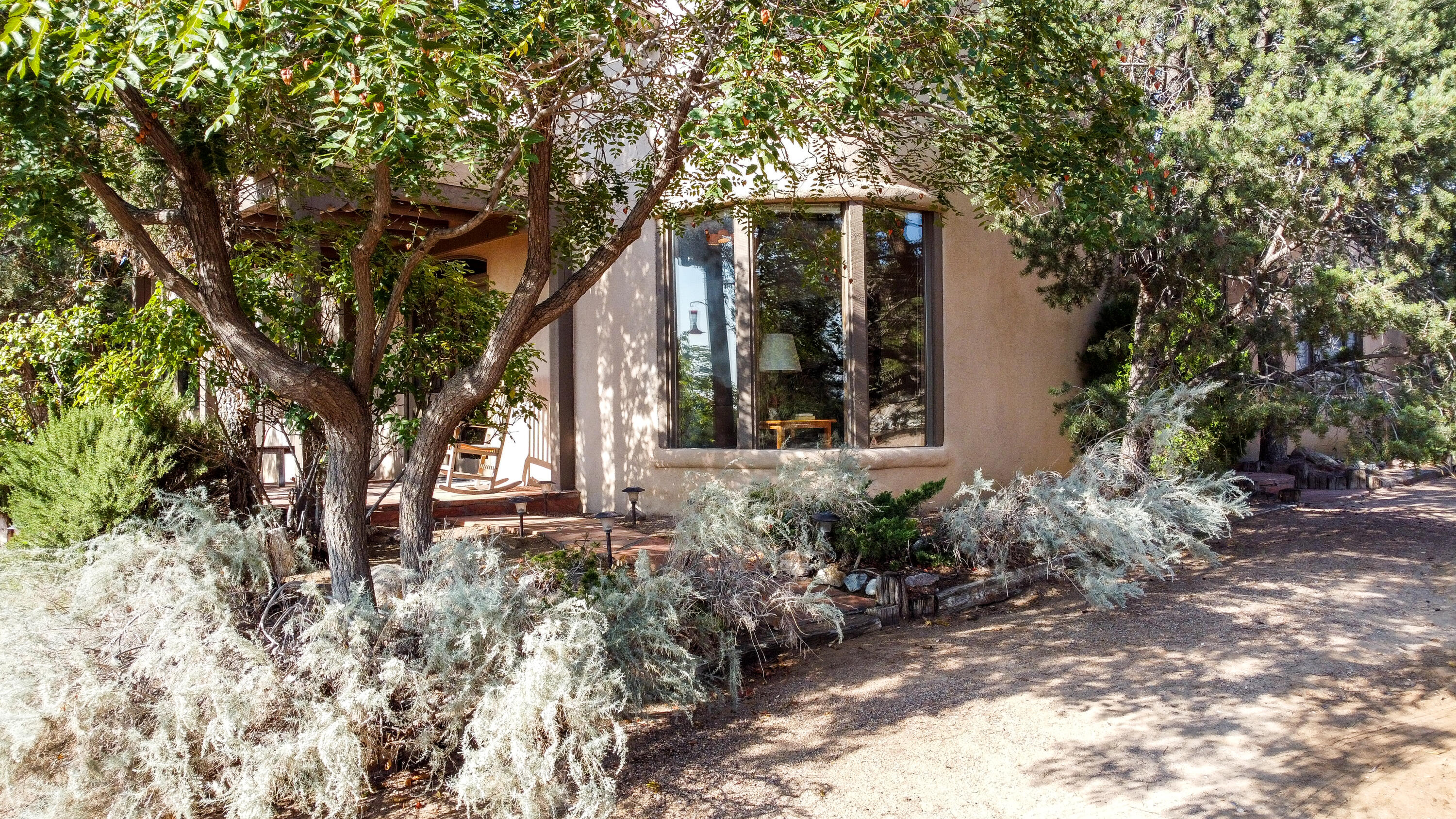 Nestled in trees, lush green shrubbery and flowers with three ponds and a stream this property is an oasis bordered by an orchard. Additionally, It has a 24'x 30' heated workshop/garage with a .75 bath and electricity, which could become a casita. Horses enjoy a 5 stall barn with tack room, a huge arena with two stalls and a 250 bale hay barn.  The lovely home has large windows throughout looking at the green gardens and the Sandia's.  Perfectly suited for entertaining it has two living areas, a kitchen with  two pantries and an island. The guest suite has its own radiant heat and 3/4 bath. This place even has its own chicken coop.  Located in a great neighborhood on the convenient south end of Corrales near shopping, restaurants, medical facilities and services.