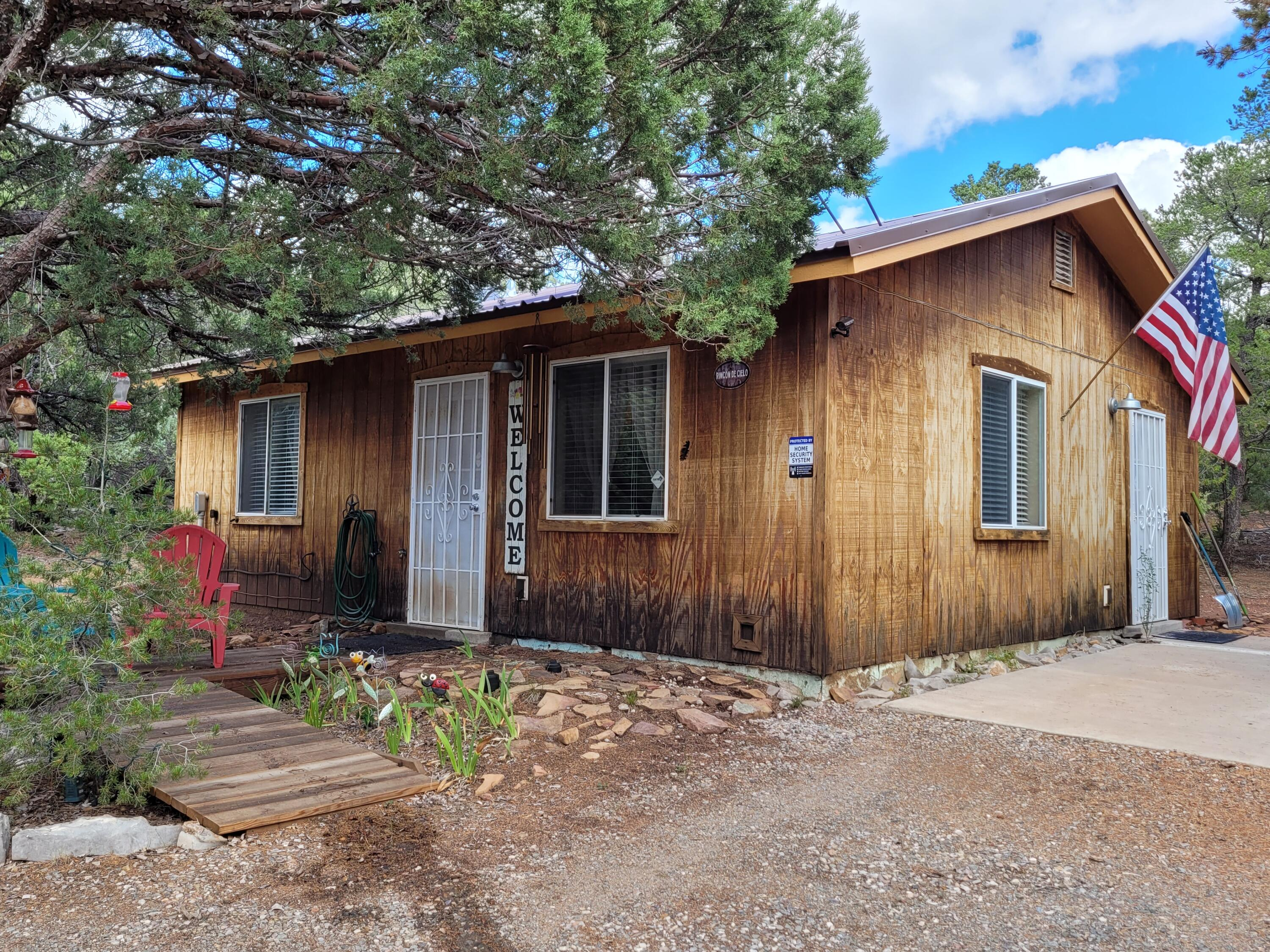 MOVE-IN READY! Adorable mountain cabin getaway in a peaceful serene forested location. Escape to the peace of your own little cabin in the forest at 7,200 feet in elevation. Located at the end of cul-de sac.  Very little traffic.  2 bedrooms, 1 bath, a good sized kitchen and living room. Great for an Air B&B. Will sell furnished/move-in ready with acceptable offer.  120 SF shed provides ample storage. Appliances included - refrigerator, range and washer. Additional possible inclusions, woodchipper, grill, 1 cord of firewood and much more!  Metal roof. 2nd bedroom/office has beautiful built in wood bookshelves and desk. New carpet.  Roads are maintained by Bernalillo county.  Don't miss out on this cabin in the woods!