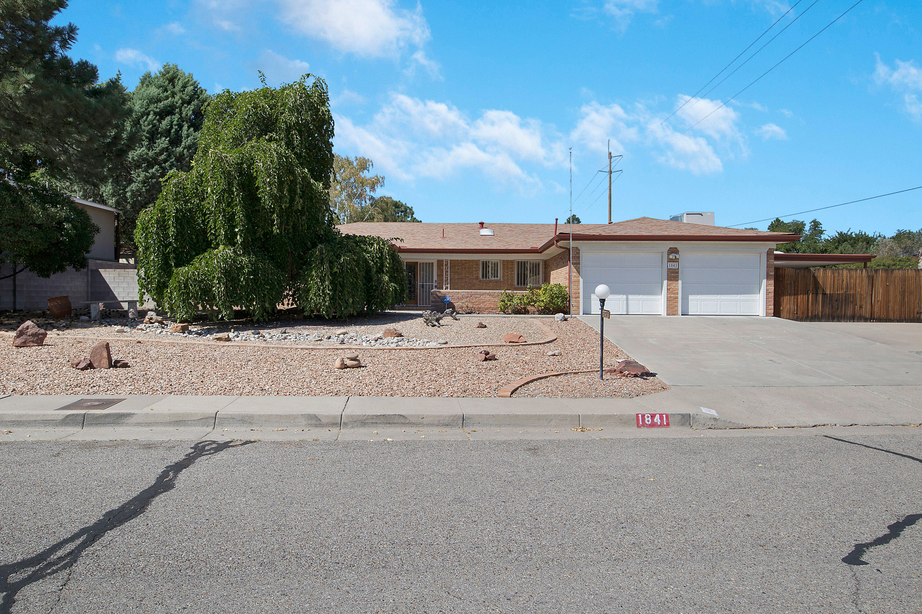 Sprawling 3 bedroom home on oversized corner lot, close to amenities and easy access to I-40. Welcoming open courtyard with beautiful mountain views. Galley-style kitchen with built in dual ovens, cooktop stove, office area, and pass through bar. Large formal living room with beam ceilings and brick fireplace. Formal dining room opens to the expansive family room with outdoor access. Primary suite boasts 5 piece master bath, jet tub, separate shower, dual sinks and closets. Gorgeous, private backyard featuring covered patio with ceiling fan and sun shades, lush lawn, trees, extra storage building/workshop with electricity and heat, and additional RV parking and carport. Move in ready!