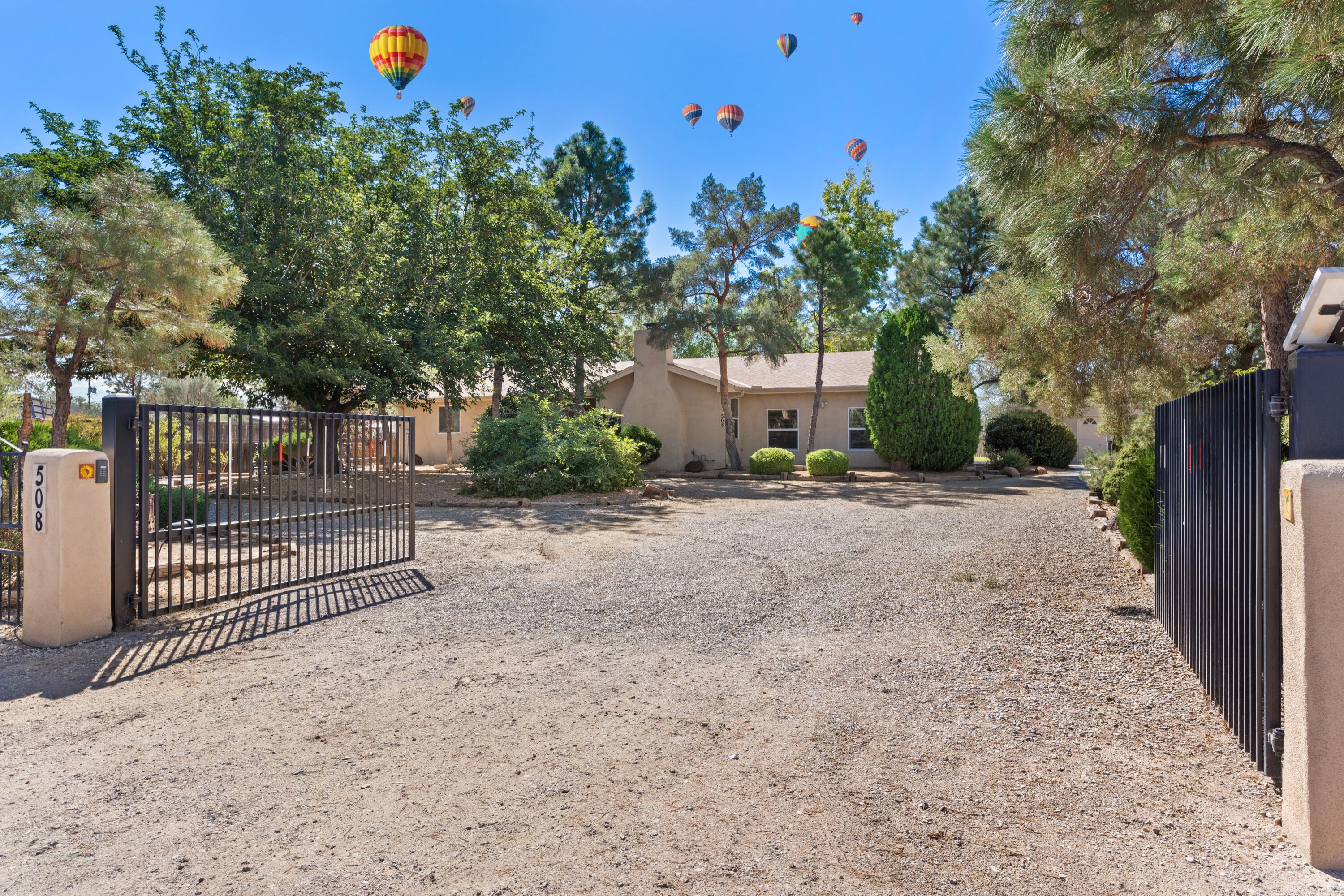 Plenty of room for your HORSES & HORSE POWER! Gorgeous approx 1.26 acre NV Village of Los Ranchos Horse Property. One of a kind, rare opportunity to own private gated valuable Sub-dividable lot. 4BD/3.5 BA renovated 2015 w/hardwood oak floors, 2015 roof, HVAC, HWH, windows, insulation, refrigerated air/heat throughout home. 1000sf grand sunroom w/ tile setting the stage for peace & relaxation. Recessed Lighting & Skylights! New SS appl! This home shines like a diamond! Not incl in TSF Finished 1979sqft  heated/cooled 6 Car Tandem Garage/Shop w/220!  The possibilities are truly endless.1100sf Horse barn, plus storage, 2 patios, circular drive w/50+ trees & fenced lawn.1 mile to Alameda Open Space, trails & Rio Grande River, & 15 mins to Airport. Perfect for entertaining. RV parking/NO HOA!