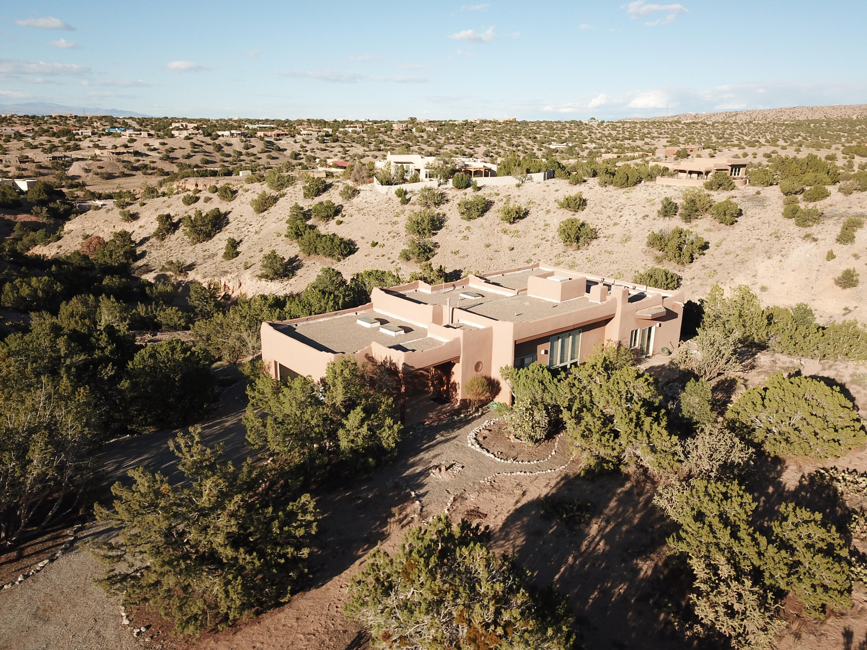 Charming southwest living in Placitas. This home has a private wooded lot.  Relax and enjoy the views from all over the property. Inside you'll find a large open floor plan that's ideal for entertaining. 14 foot exposed beam ceilings and two wood burning kiva fireplaces. Move-in Ready! Come see before it's gone.