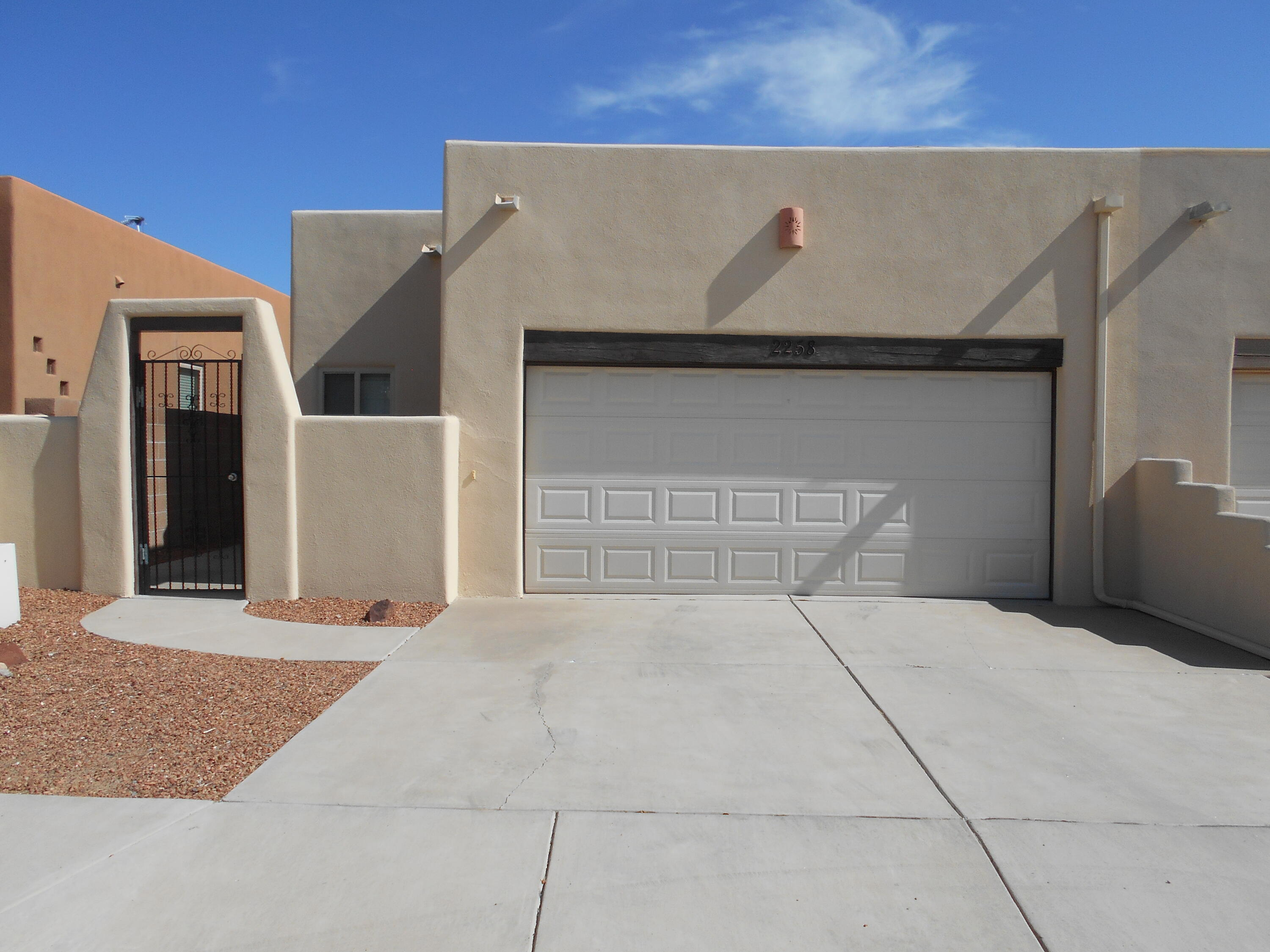 Gorgeous Pueblo style townhouse in a gated community. Exquisite beamed tongue & groove ceiling in LR. Laminate flooring in kitchen , dining room, and hallway. Tile in bathrooms. Carpet in LR and 2 bedrooms. Tile counter tops in kitchen. Beautiful cabinets in kitchen and bathrooms. Double vanity, shower and linen cabinet in MB bathroom. Pocket doors in second bathroom. Gas log fireplace. Skylights. Nicely landscaped. Covered patio. New TPO roof installed in December 2020 ( warranty included). Stucco repainted in July 2021. Attached townhome. 2 car garage. There are 2 wall heaters in the garage.